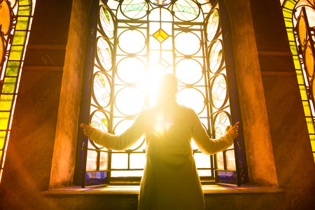 52647725 - religious christian woman looking trough the stained glass church window light.woman praying to god at st. alexander nevsky cathedral.finding serenity in religion,faith and hope concept.enlightenment